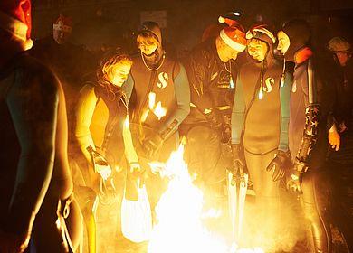 Ein beliebtes Event an der Mosel im Winter ist das Fackelschwimmen in Bernkastel-Kues. Nach dem Schwimmen durch die eisige Mosel wärmen sich die Taucher an einem offenen Feuer.